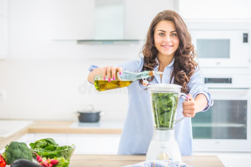 Woman making vegetable soup or smoothies with blender in her kitchen. Young happy woman preparing healthy food or drink with olive royalty free stock photography