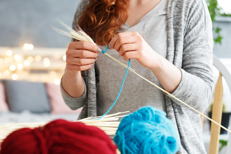 Woman making yarn decorations. Young woman making colorful creative yarn decorations stock photo