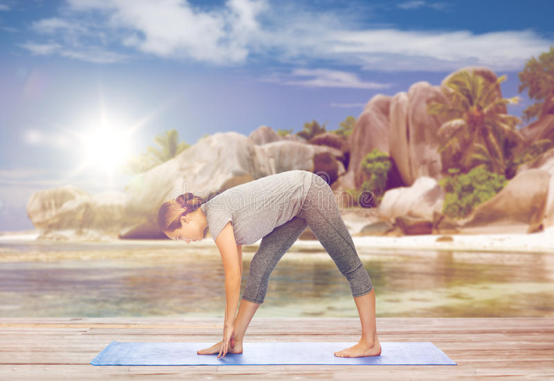 Woman making yoga intense stretch pose on beach royalty free stock images