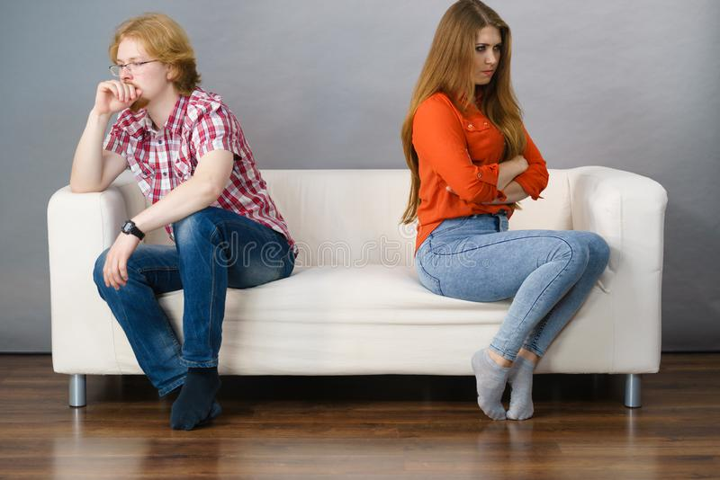 Woman and man after argue on sofa. Man and women being mad, ignoring each other after fight. Friendship, couple breakup difficulties and problems concept royalty free stock photos