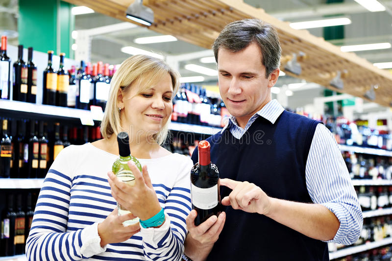 Woman and man with bottle of wine in store stock photography