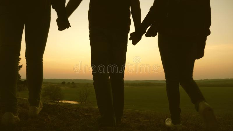 Woman, man and child travel, enjoy scenery at sunset, raise hands up. Freedom. Travelers family travel with backpacks royalty free stock photography