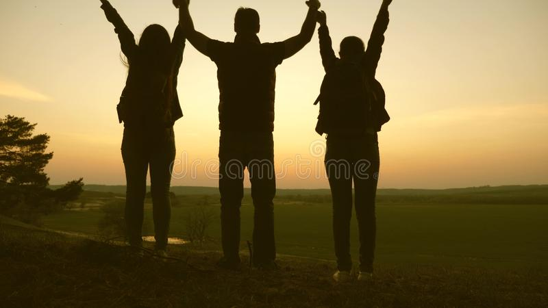 Woman, man and child travel, enjoy scenery at sunset, raise hands up. Freedom. Travelers family travel with backpacks stock photo