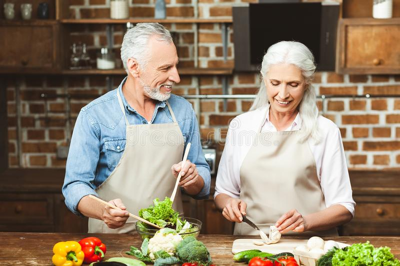 Woman and man cooking healthy food. Attractive women and men cooking healthy food for dinner together royalty free stock photography