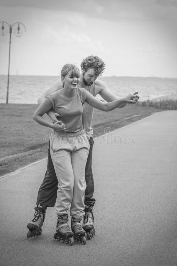Woman and man couple rollerskates outdoor royalty free stock image