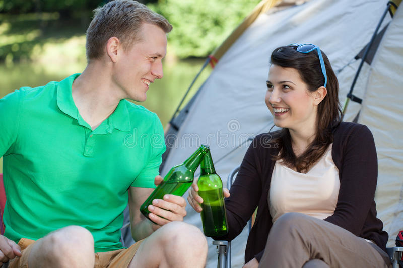 Woman and man drinking beer. Woman and men drinking beer on camping stock photo