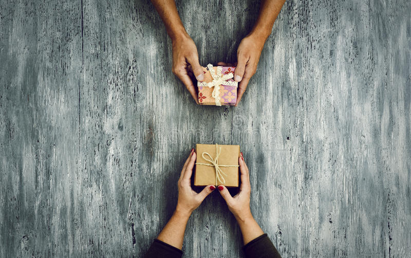 Woman and man exchanging gifts. High-angle shot of a young caucasian woman and a young caucasian man exchanging gifts on a rustic wooden table, with some royalty free stock photos