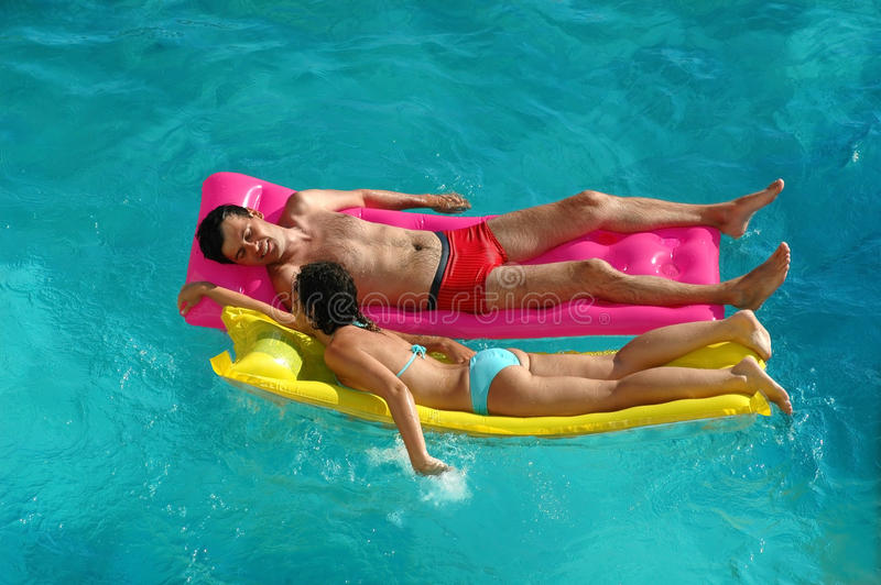 Woman and the man floating on a mattress royalty free stock image