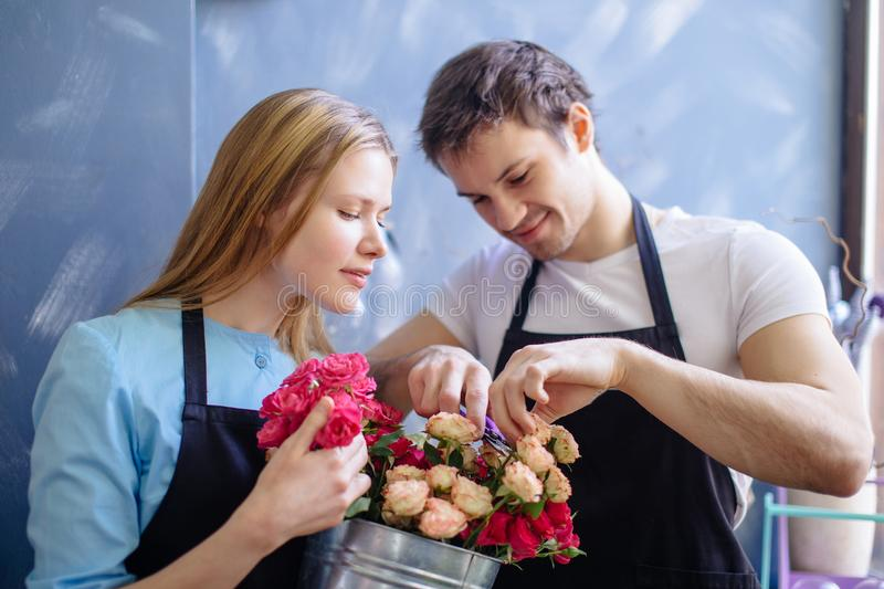 Woman and man helping each other to deccorate flowers. Woman and men helping each other to deccorate flowers in floristic shop stock photos