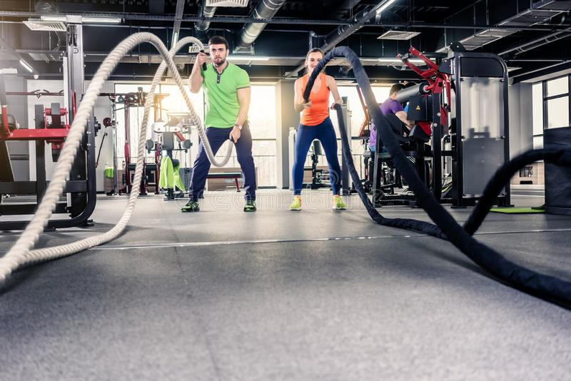 Woman and man holding rope at gym stock image