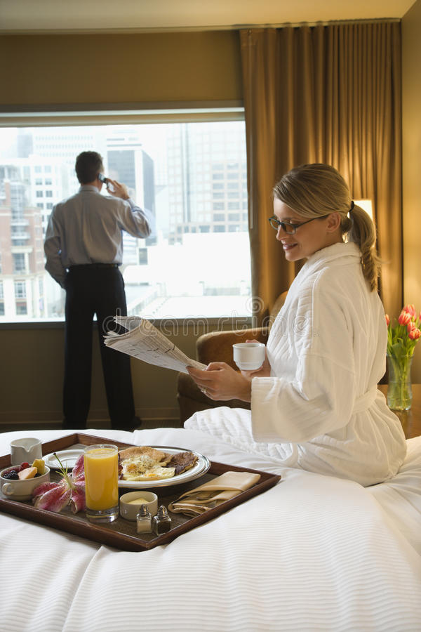 Woman and Man in Hotel Room. Caucasian woman in a robe sits on a hotel bed while reading the newspaper. A man stands in the background talking on his mobile royalty free stock photo