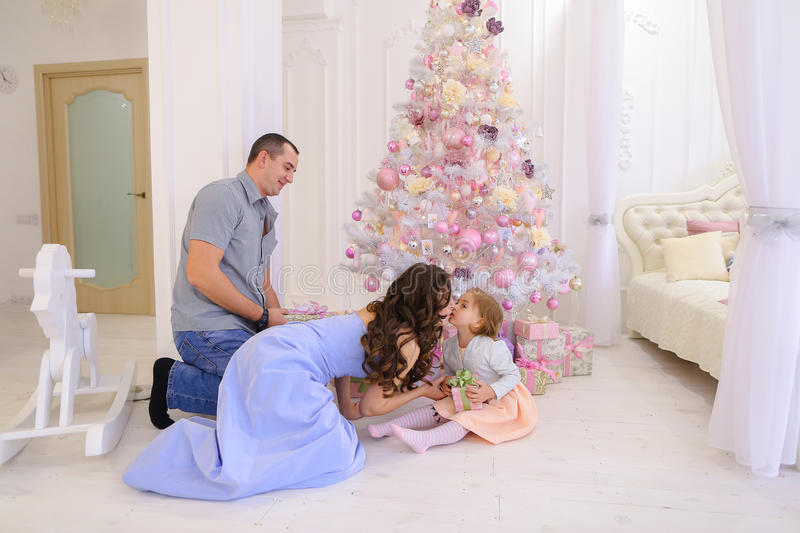 Woman, man and little girl hand Christmas presents its half in s stock image
