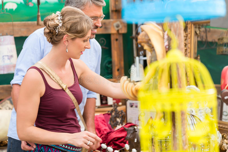 Woman and man looking for antiques at flea market stock images