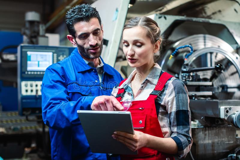 Woman and man manufacturing worker in discussion. Woman and men manufacturing worker in discussion writing on tablet computer royalty free stock photography