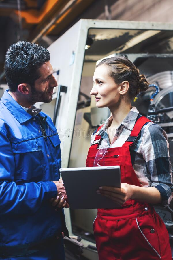 Woman and man manufacturing worker in discussion. Woman and men manufacturing worker in discussion writing on tablet computer royalty free stock photos