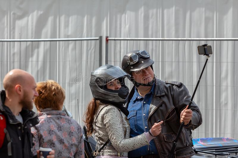 Happy and smiling woman and man motorcyclists in helmets take selfie using smartphone with a sliding monopod royalty free stock photos