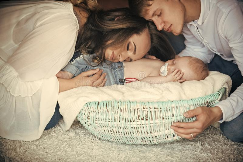 Woman, man and newborn child sleep in crib on floor. Woman, men and newborn child sleep in crib on floor. Mother, father hug basket with baby son asleep. Family royalty free stock photos