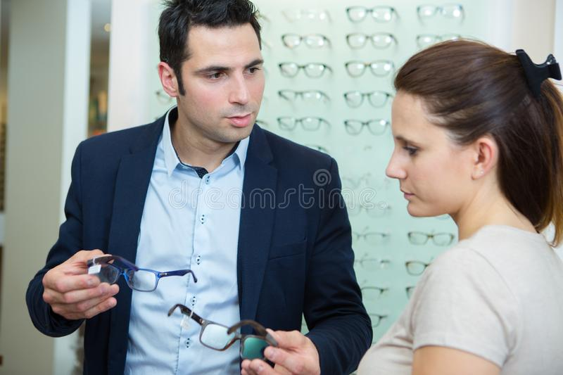 Woman and man in optician shop discussing price for glasses royalty free stock photos