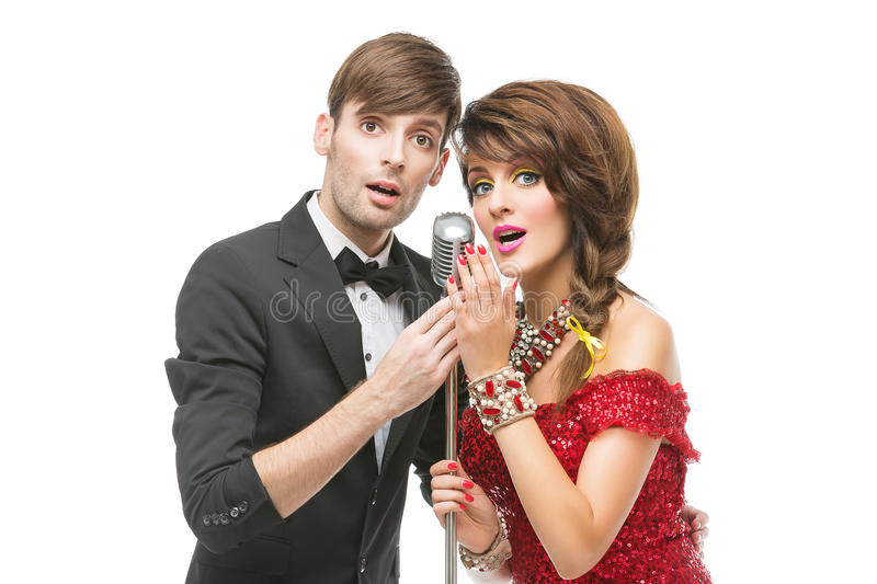 Woman and man performing song in retro microphone stock photography