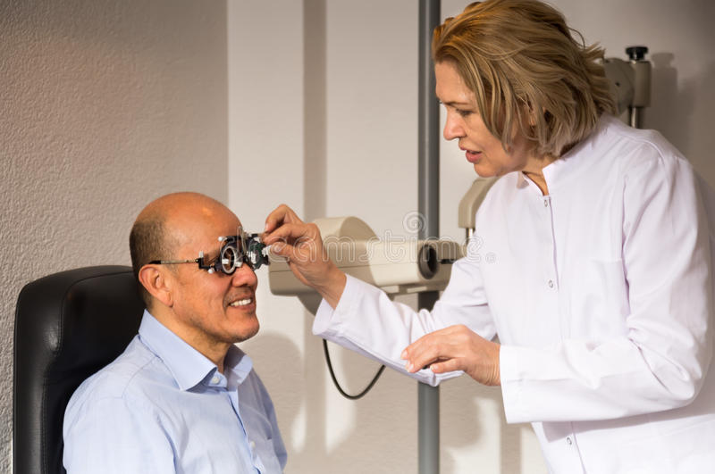 Woman and man retired ophthalmologist check eyesight in clinic royalty free stock photo