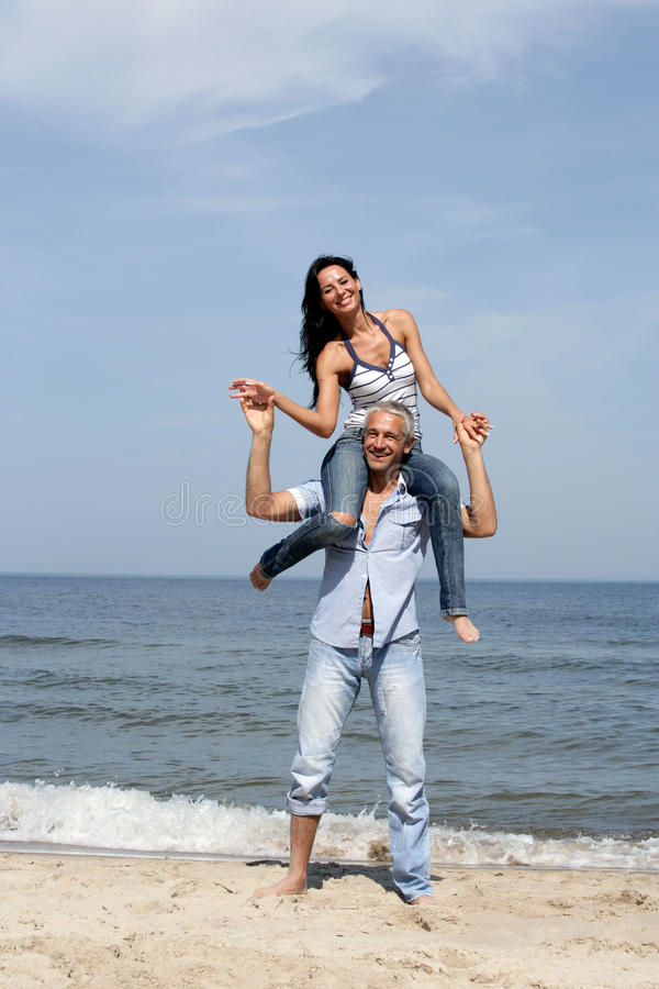 Woman on man's shoulders. Mature woman riding on man's shoulders on a beach royalty free stock images