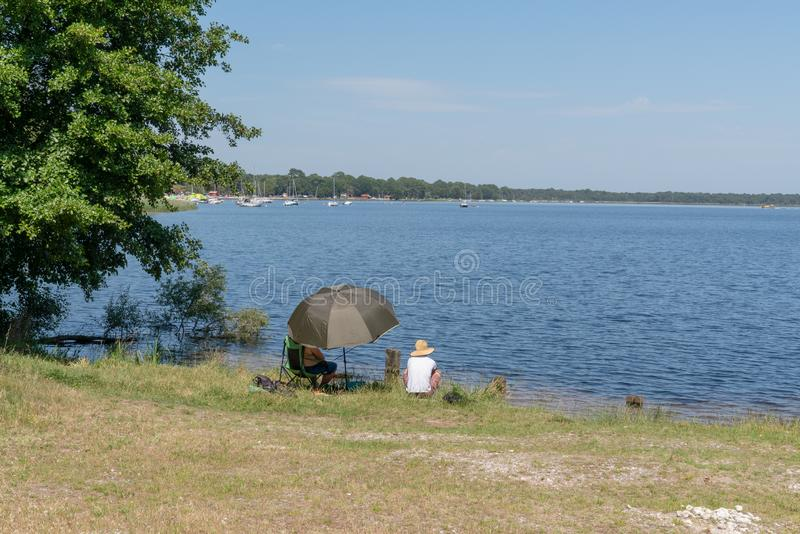 Woman and man seated next to the lake fishing and relaxing in Lacanau France royalty free stock images