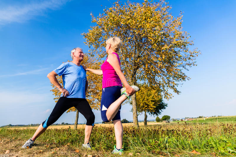 Woman and man, seniors, doing sport outdoors. In the grass on meadow royalty free stock photography