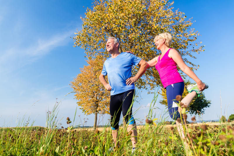 Woman and man, seniors, doing sport outdoors. In the grass on meadow stock photo