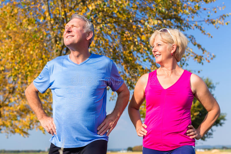 Woman and man, seniors, doing sport outdoors. In the grass on meadow stock image