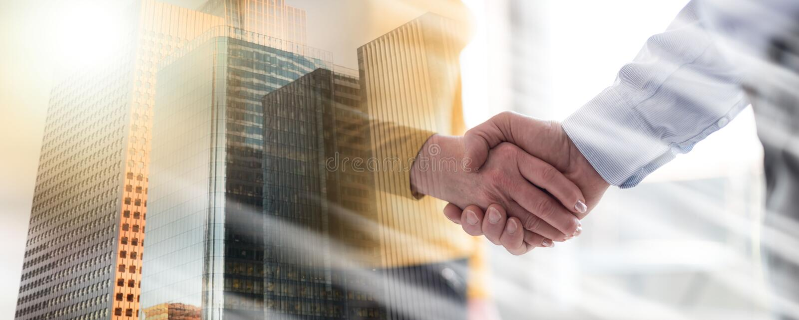 Woman and man shaking hands in office, light rays effect; multiple exposure. Businesswoman and businessman shaking hands in office, light rays effect; multiple royalty free stock photography