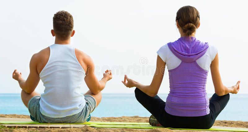 Download Woman And Man Sitting Cross-legged Do Yoga Poses On Beach Stock Photo - Image: 83702042