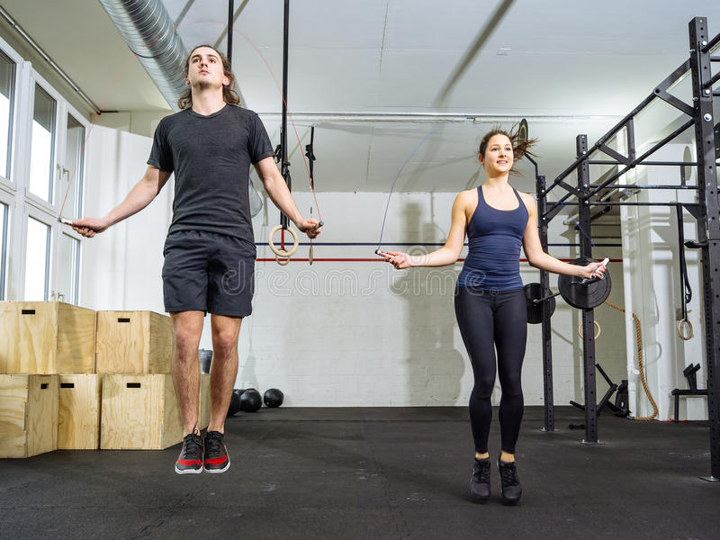 Woman and man skipping rope at the gym stock image