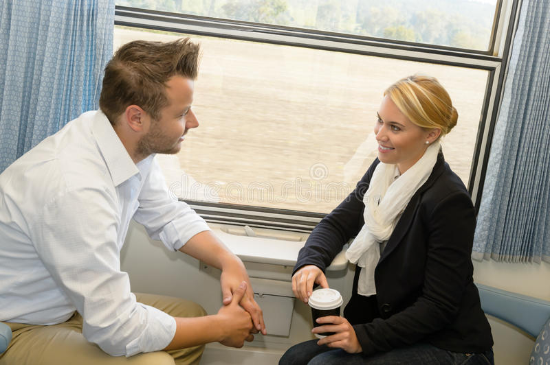 Woman and man traveling with train talking stock photography