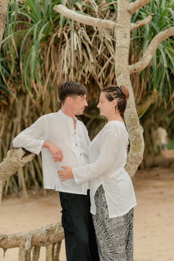 A woman with a man under a palm tree. Indian clothes are a women with a men under a palm tree stock photos