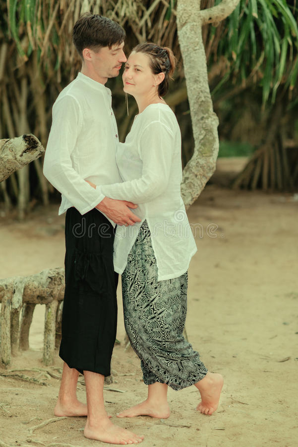 A woman with a man under a palm tree. Indian clothes are a women with a men under a palm tree stock images