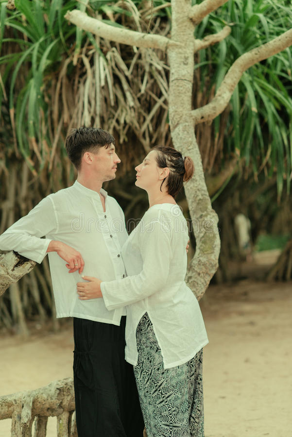 A woman with a man under a palm tree. Indian clothes are a women with a men under a palm tree royalty free stock photo