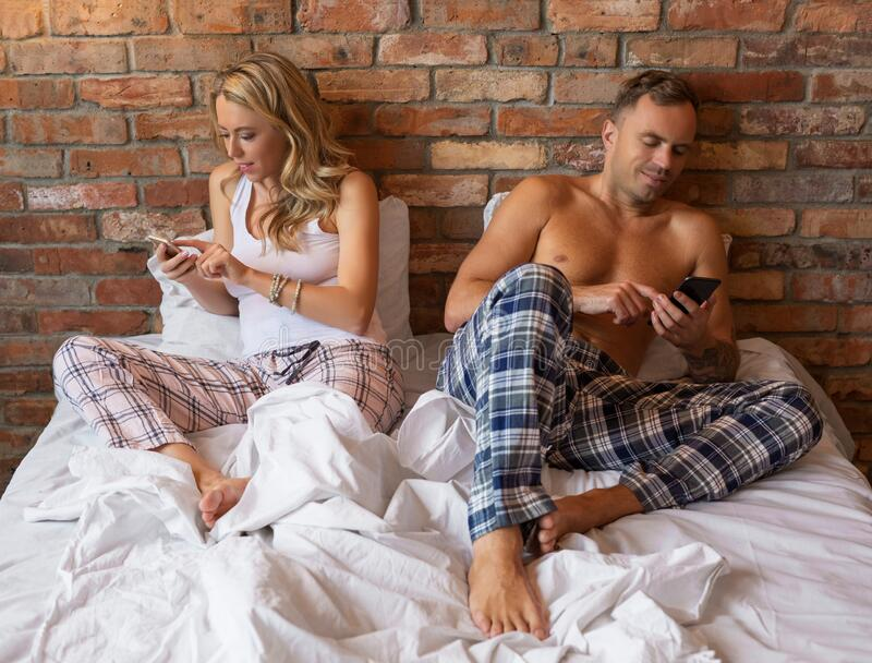 Woman and man using their mobile phones in bed stock photography