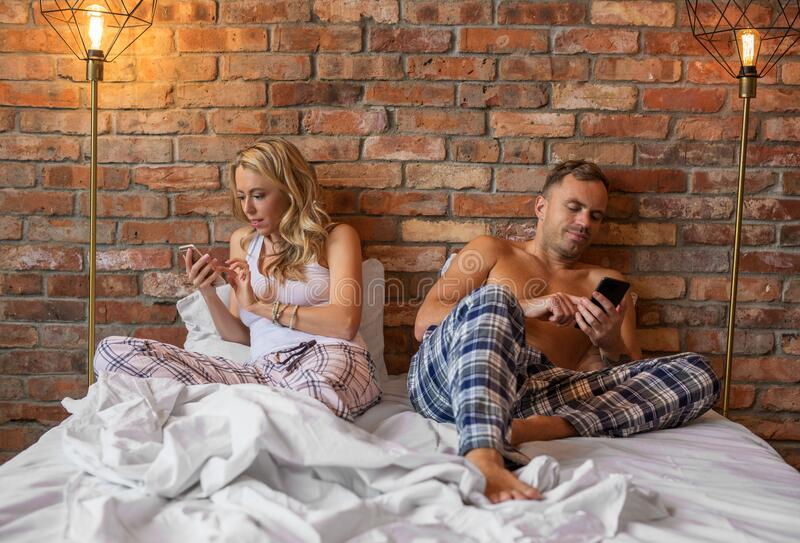 Woman and man using their mobile phones in bed royalty free stock images