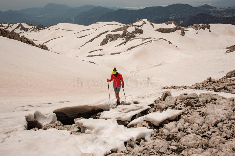 Woman and man walking on the dirty snow on the Tahtali mountain with hiking sticks royalty free stock photography