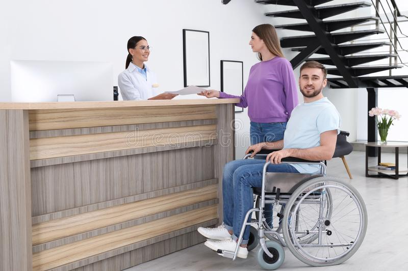 Woman with man in wheelchair near receptionist royalty free stock photos