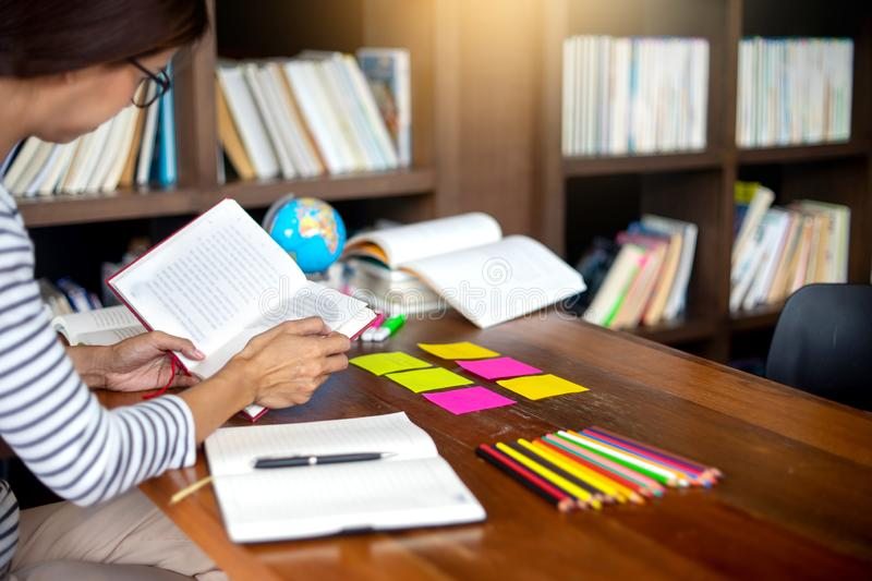 Woman and man work for education or business on the table. Woman work for education or business she read a book and on the table there are paper work color pen royalty free stock images