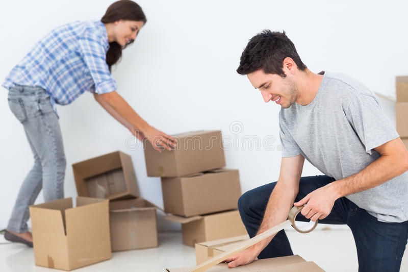 Woman and man wrapping boxes stock photography