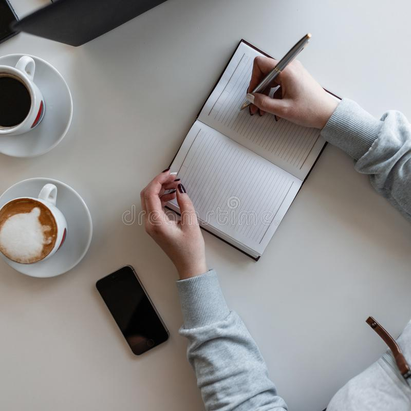 Woman manager sits at a white table at a business meeting in a modern office with a executive, listens to him attentively. And takes notes in a notebook. Close stock images
