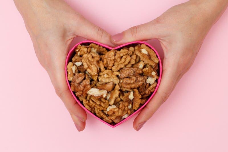 Woman& x27; mano de s que sostiene una caja en forma del corazón con las nueces peladas en fondo rosado imágenes de archivo libres de regalías