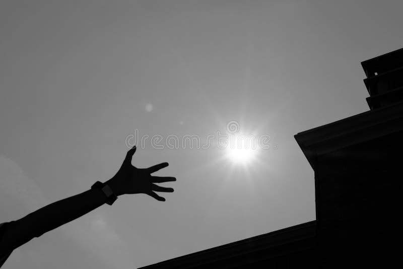 woman& x27; mano di s che raggiunge per il sole con la siluetta di buil moderno fotografia stock libera da diritti