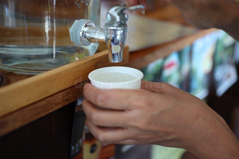 Woman& x27; mano di s che tiene un bicchiere d'acqua che preme dalla brocca di vetro immagini stock libere da diritti