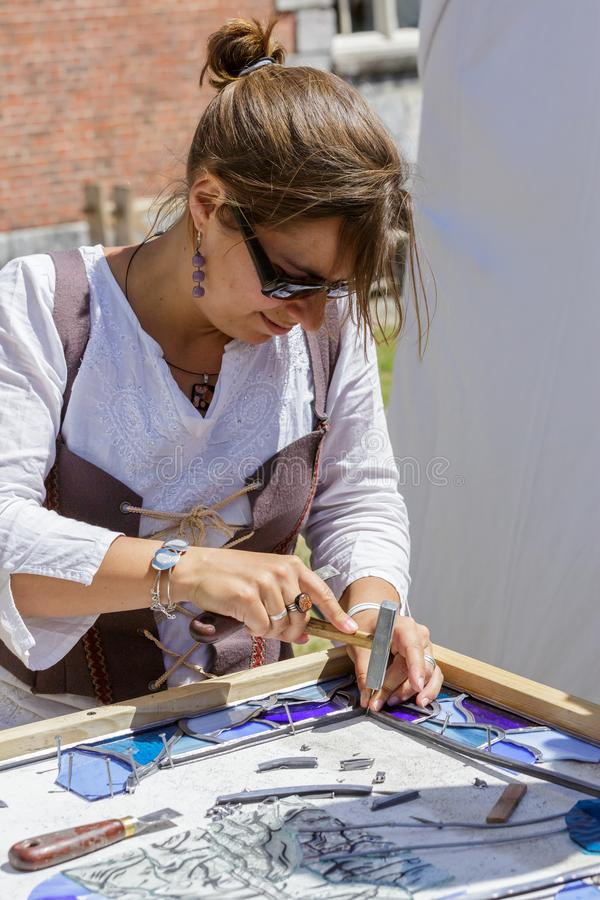 Woman manufacturer working with stain glass stock image
