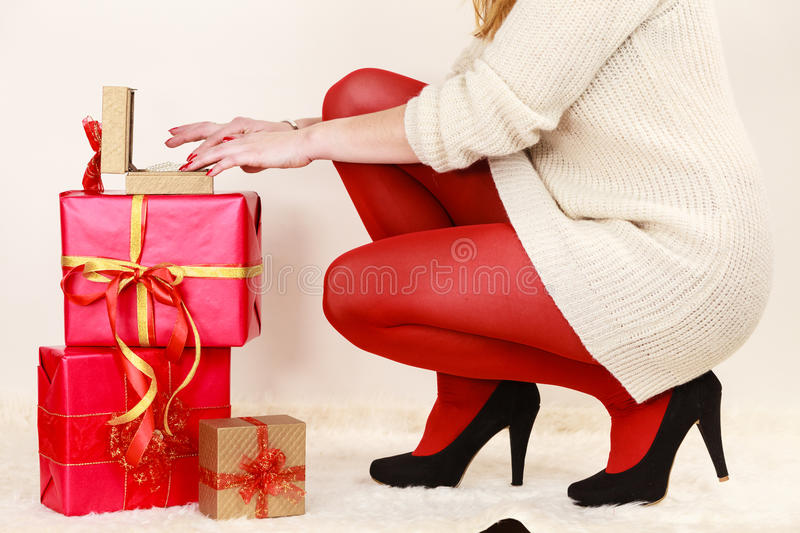 Woman with many gift boxes opening golden box with jewel pearls royalty free stock images