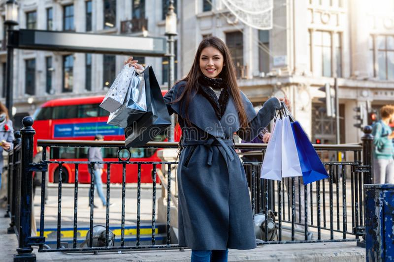 A woman with many shopping bags in her hand in the center of London, United Kingddom. A attractive woman with many shopping bags in her hand in the center of stock image