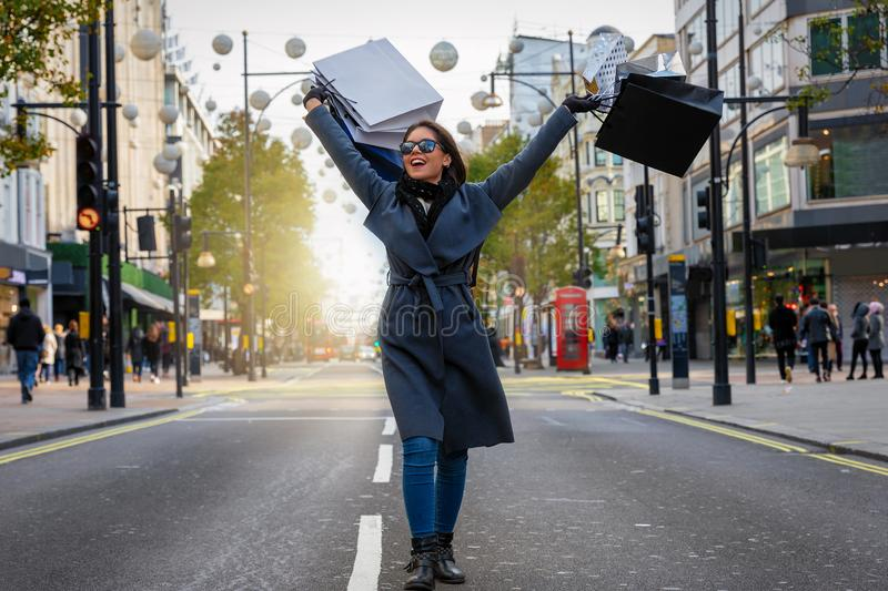 Woman with many shopping bags in her hand walking down Oxford Street stock images